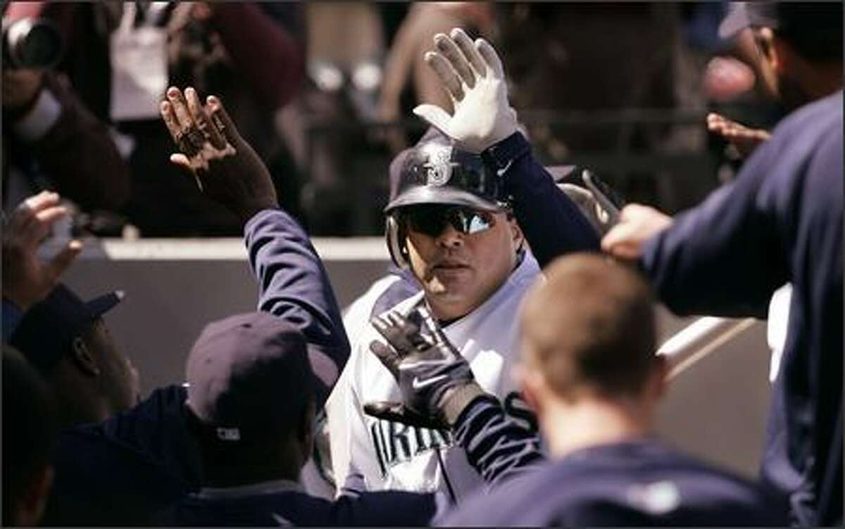 Seattle Mariners' Jose Vidro returns to the dugout following his 3-run home run against the Texas Rangers in the second inning. (AP Photo/Elaine Thompson)