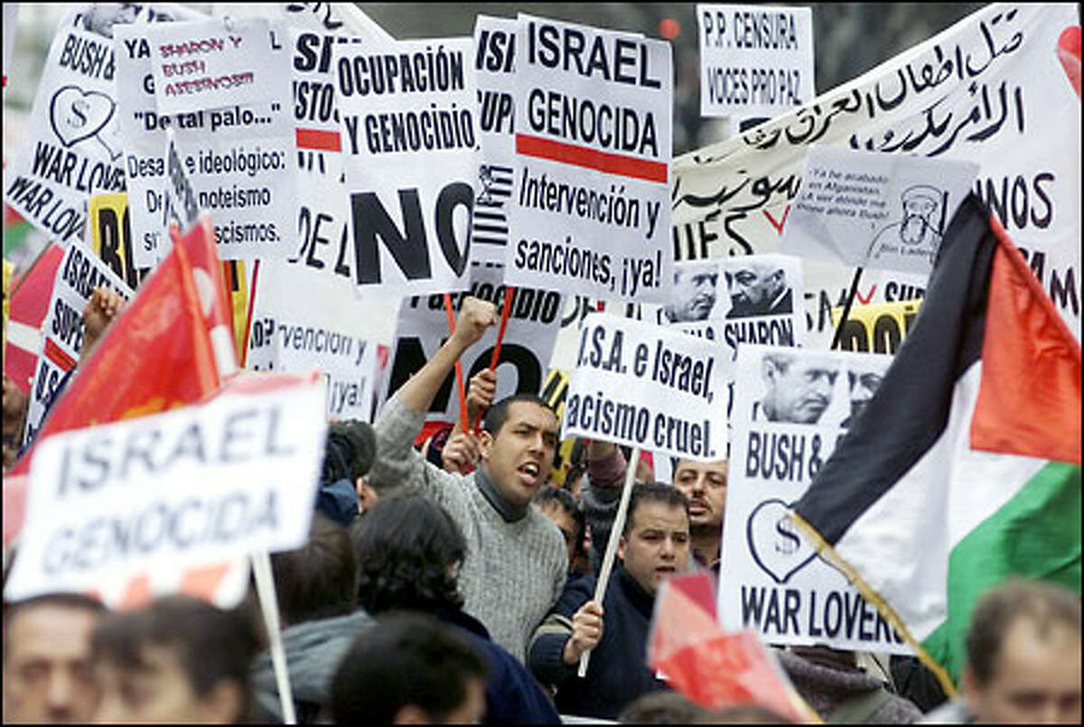 Protesters carry a variety of banners during an anti-Israeli demonstration yesterday in Madrid, Spain. The rally was organized to oppose the Israeli army's incursion into Palestinian Authority territory.