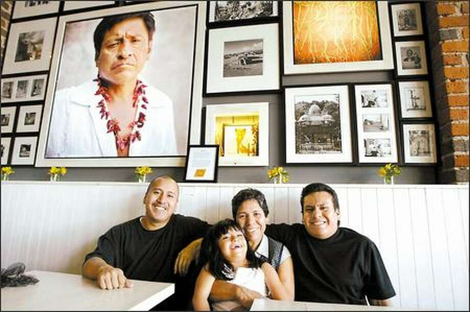 Spike Mafford photos line the wall behind owners Roberto, left, and Misael Dominguez and their mother, Gloria Perez Montesinos, who holds granddaughter Gloria Dominguez. Photo: Meryl Schenker, Seattle Post-Intelligencer / Seattle Post-Intelligencer