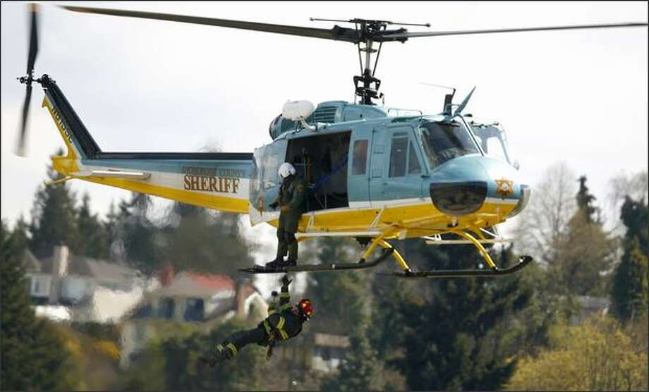 A member of the Seattle Fire Department reaches for the skid of a Snohomish County Sheriff's helicopter during rescue training on Wednesday at the Seattle Joint Training Facility on Myers Way South.  The drill, used to prepare both departments for regional disasters, would help rescuers reach high rise buildings and other hard-to reach locations. Photo: Joshua Trujillo, Seattlepi.com / seattlepi.com