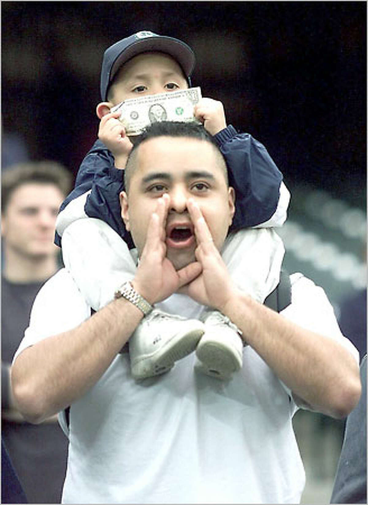 Nathan Trujillo Jr., 5, holds up a dollar bill and joins his father Nathan in booing Alex Rodriguez, who left the Seattle Mariners in a $252 million deal with the Texas Rangers.