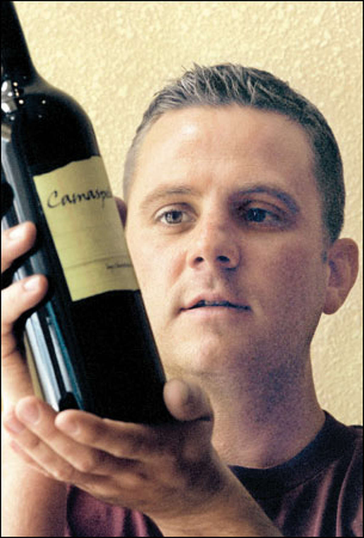 Christophe Baron, holding a bottle of Camaspelo from his Cayuse Vineyards near Walla Walla.