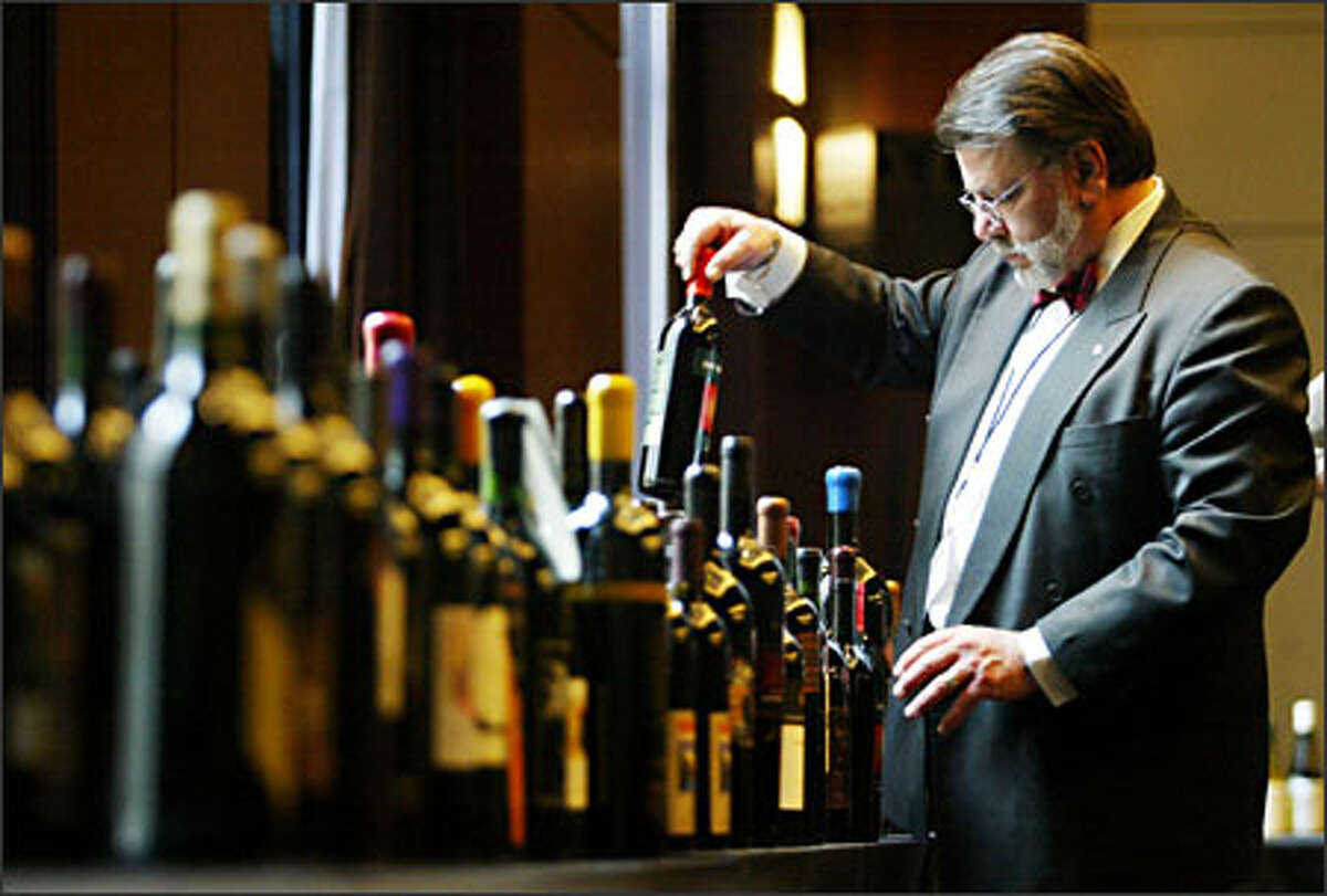 Washington Athletic Club sommelier Robert Bonina prepares bottles for tasting at the MAGNUM event at the W Hotel in downtown Seattle.