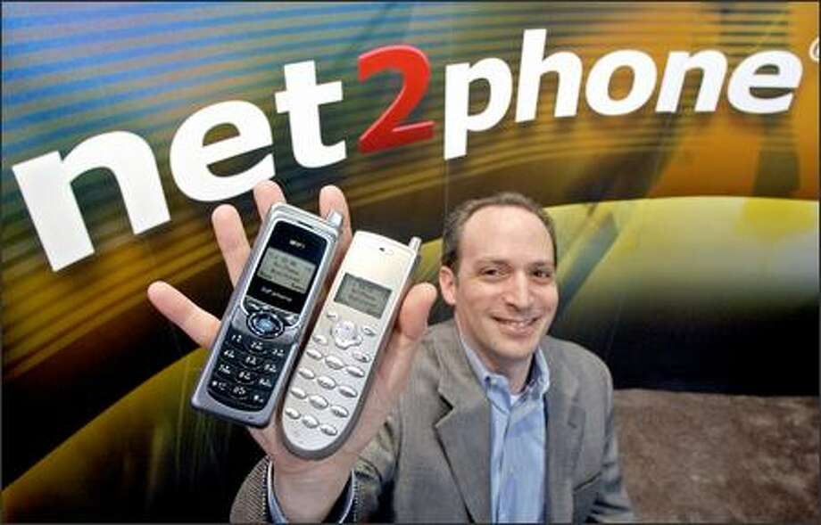 David Span, Senior Vice President of Net2Phone, holds up two of his VoIP (voice over Internet Protocol) devices that use wi-fi at a San Jose, Calif., tradeshow on March 14. As Internet telephony grows more popular, a number of companies are battling to be the 21st century equivalent of Ma Bell. (AP Photo/Paul Sakuma) Photo: Associated Press / Associated Press