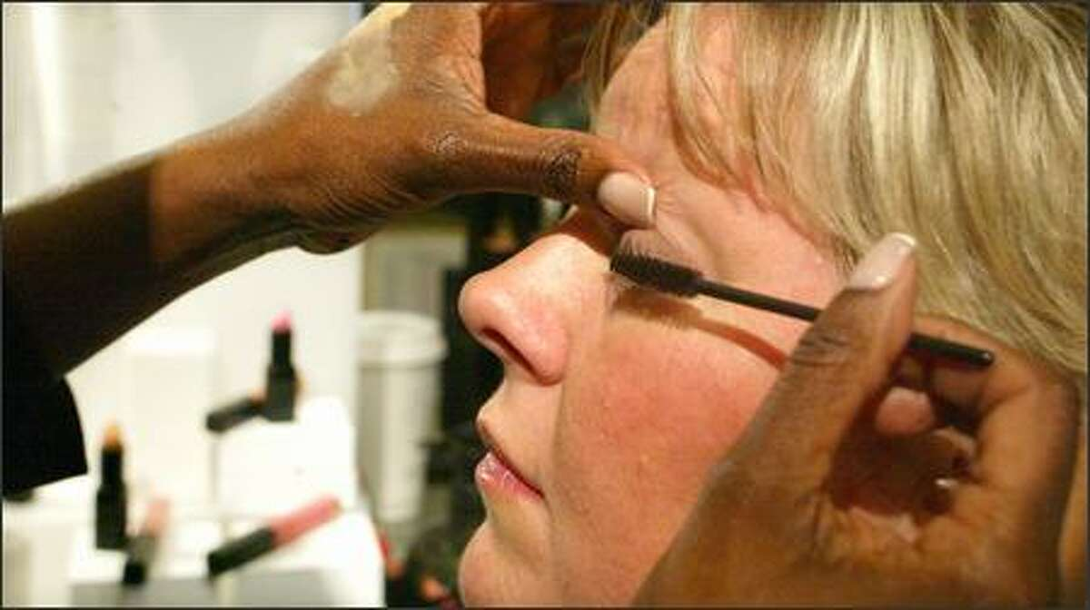 Uzo applies mascara to Linda Johnson's eyelash at Barneys New York. Uzo has powder smeared on the back of her left hand, which she uses as her palette. This practice warms the makeup to body temperature and allows the artist easy access to, and prevents overuse of, the product.