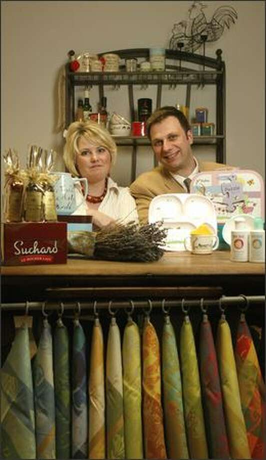 Lisa and Hugues Deriau display some of The Frenchy Bee's products, including French kitchen towels. Photo: Joshua Trujillo, Seattlepi.com / seattlepi.com