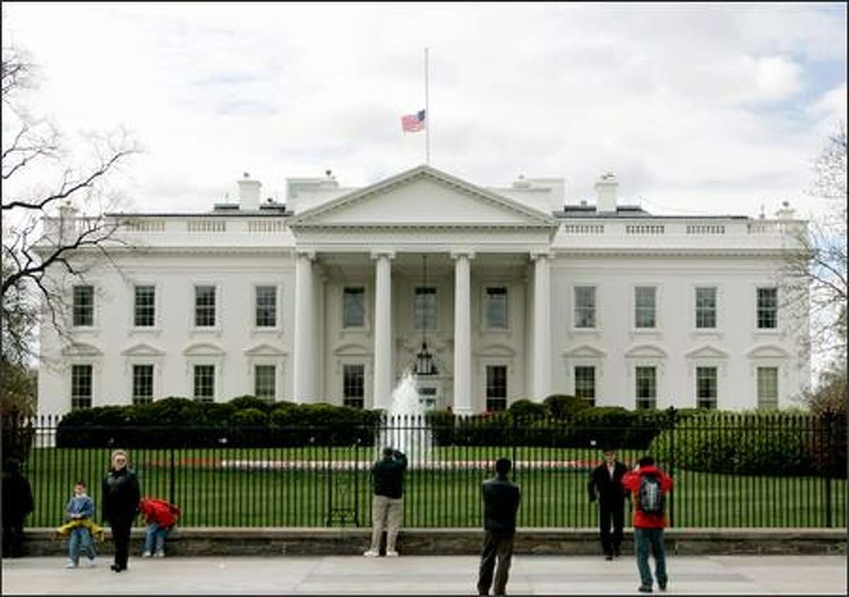 Visitors gather in front of the White House Tuesday see the U.S. flag at half-staff after President Bush ordered flags to be lowered in honor of those killed at Virginia Tech. (AP Photo/Pablo Martinez Monsivais)