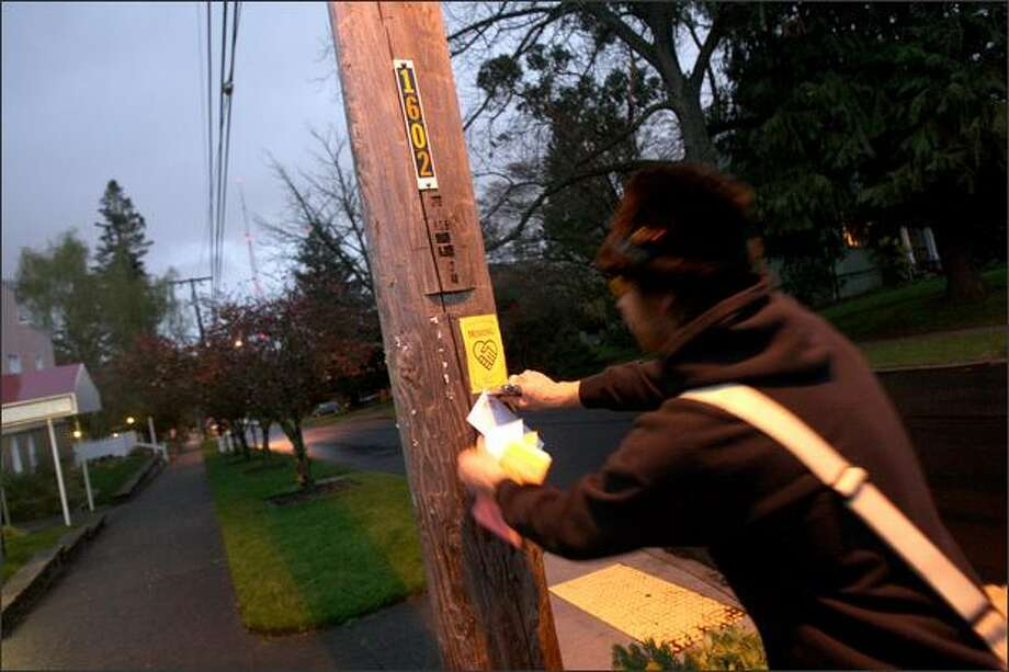 Queen Anne resident Gabe Johnson staples fliers and copies of an essay by Hunter S. Thompson to telephone poles Tuesday. He's a member of a group called the Comstock Commission, which is trying to promote creative interaction among a Queen Anne set it sees as a bit stuffy. Photo: Mike Kane, Seattle Post-Intelligencer / Seattle Post-Intelligencer