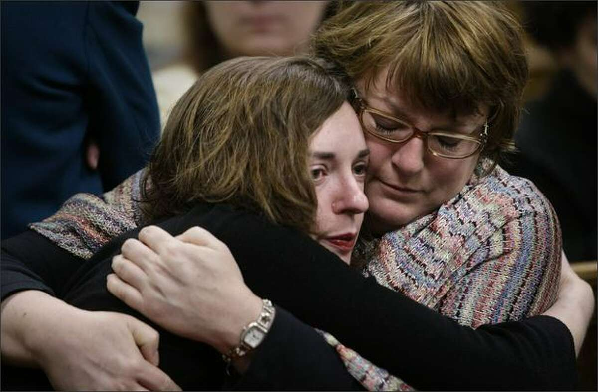 Cheryl Stumbo, right, a survivor of the shootings a the Jewish Federation of Greater Seattle, and Rachel Hynes, a current employee of the charity, comfort one another during the testimony of Christina Rexroad. Rexroad recounted how she nearly died after being shot in the abdomen.