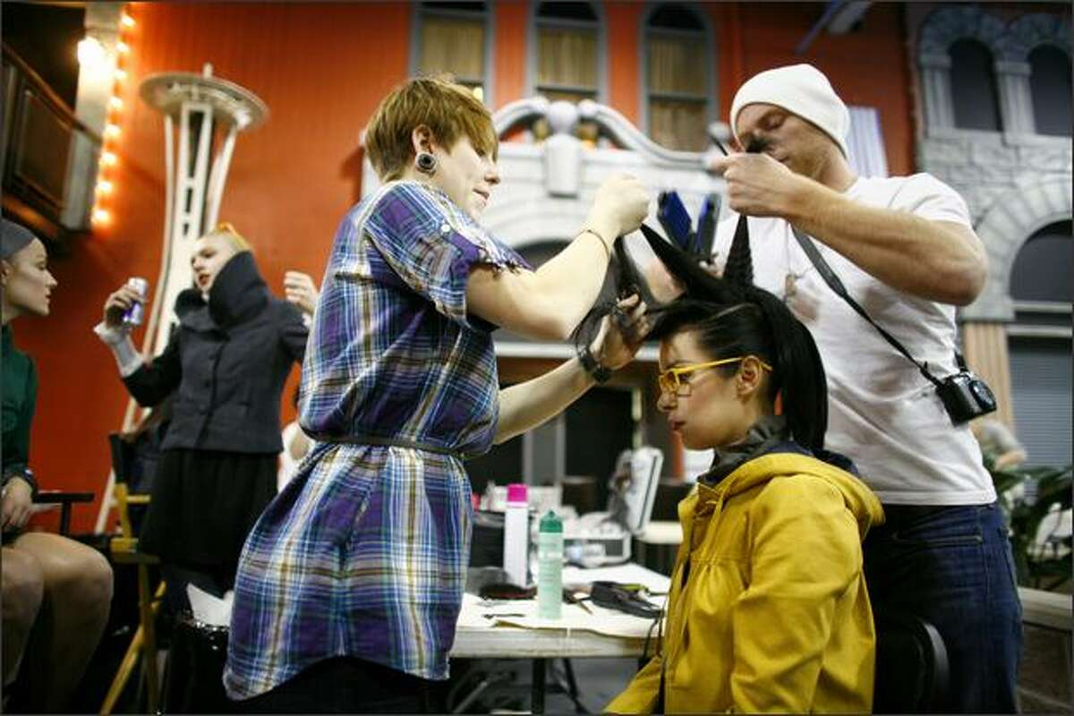 Model Lola Rebollo has her hair styled by Anne Jordan and Charlie Perritt backstage at Seattle Fashion Week's Independent Designers Showcase show on Thursday at Fremont Studios in Seattle.