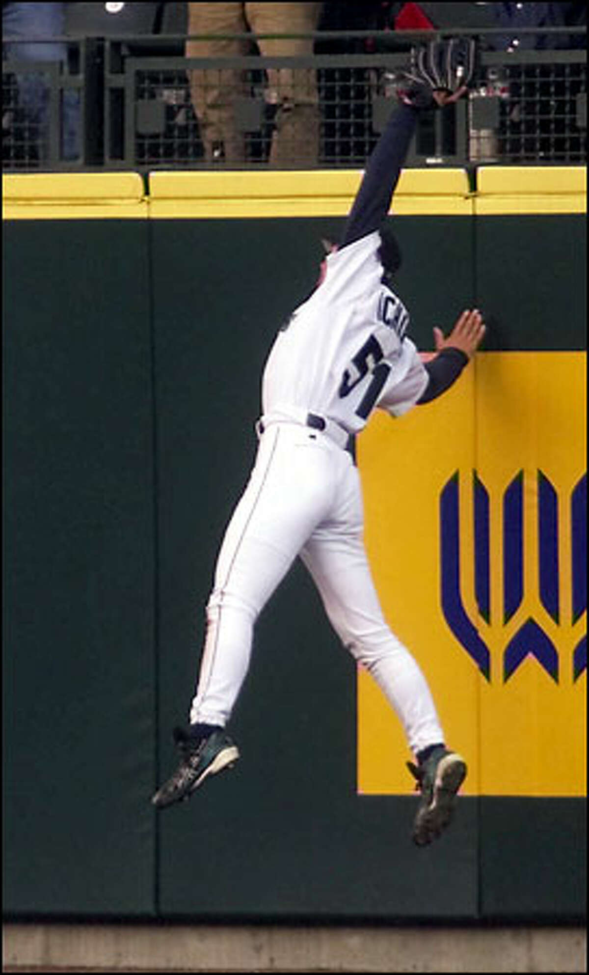 Mariners right fielder Ichiro Suzuki leaps at the wall to rob Rafael Palmeiro of a home run in the second inning.