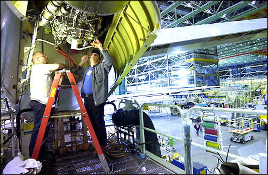 Boeing mechanic Steve Karbo, left, watches as Robert Klinefelter inspects his work on an auxiliary power unit of a 747 at the Everett plant. The company has consolidated production to cut costs. Photo: Associated Press / Associated Press