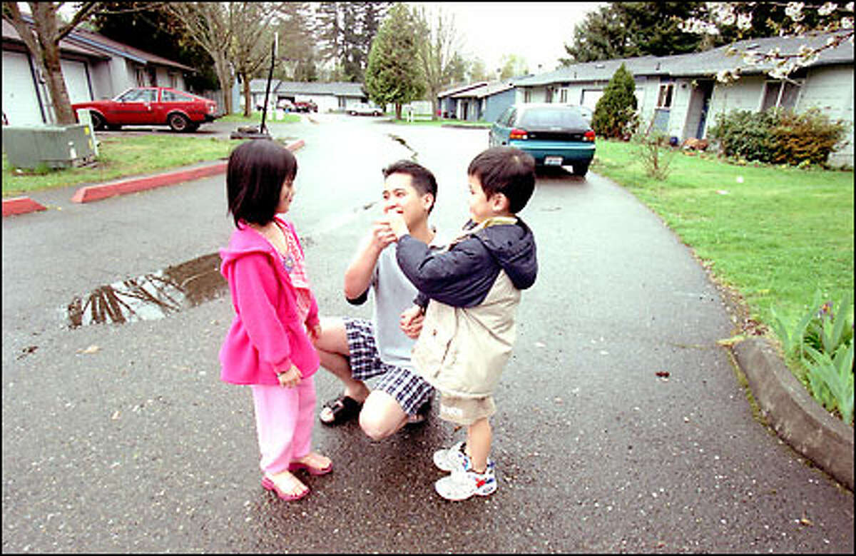 Puan Tran talks with his children, Terri, 6, and David, 5, recently near their home in Benson East on Southeast 223rd Place in Kent. The Benson East residents banded together to buy their entire neighborhood.