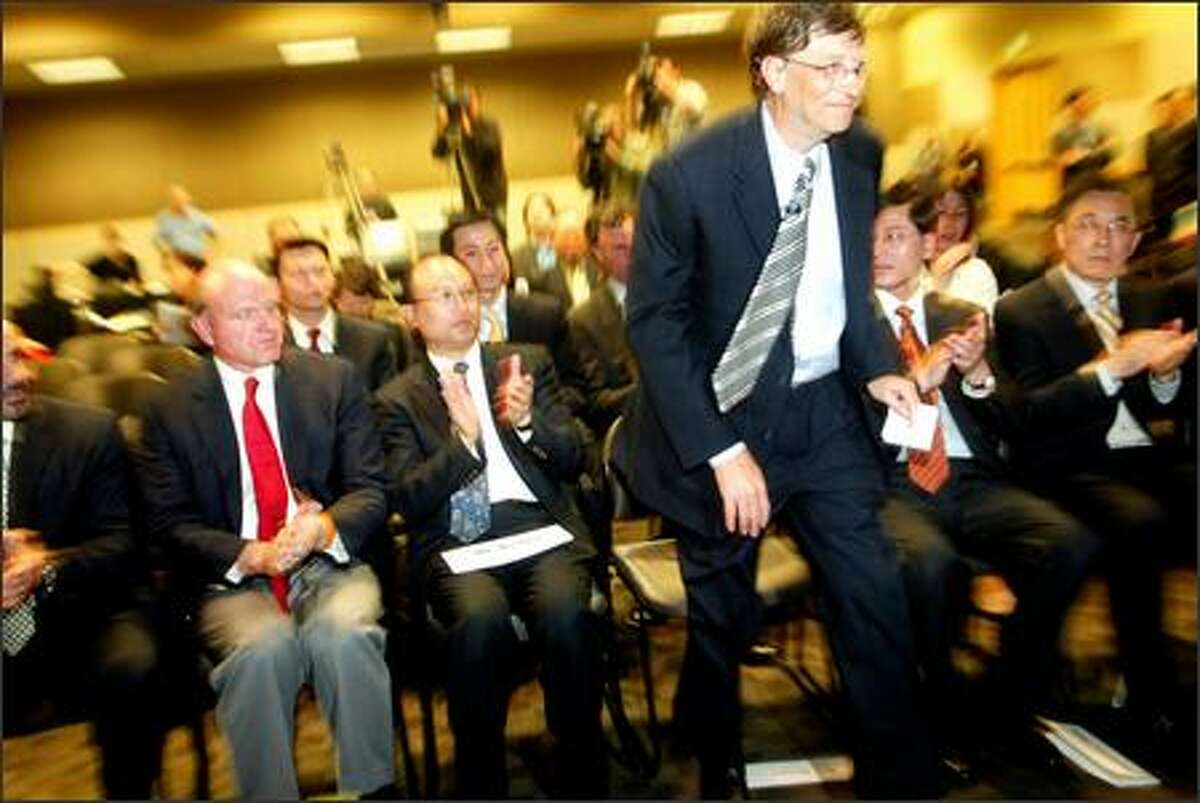 Bill Gates gets up to speak at Microsoft in Redmond on Monday. From left are Microsoft's Steve Ballmer, China's Xu Qin, Lenovo's Yang Yuanqing and China's Ma Xin.
