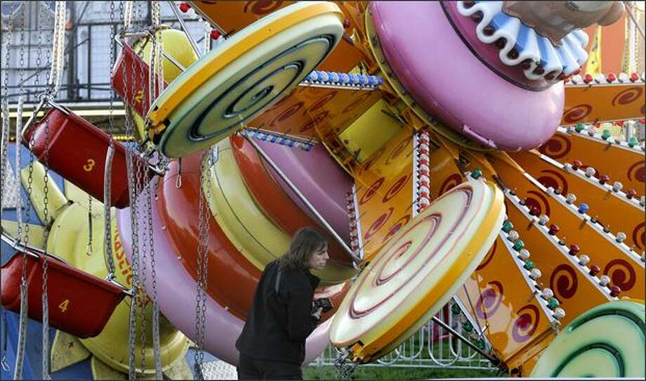 A Puyallup police officer investigates the Lolli Swing ride after it fell over with children on it Friday at the Puyallup Spring Fair. (AP Photo/Joe Barrentine/The News Tribune) Photo: Associated Press / Associated Press