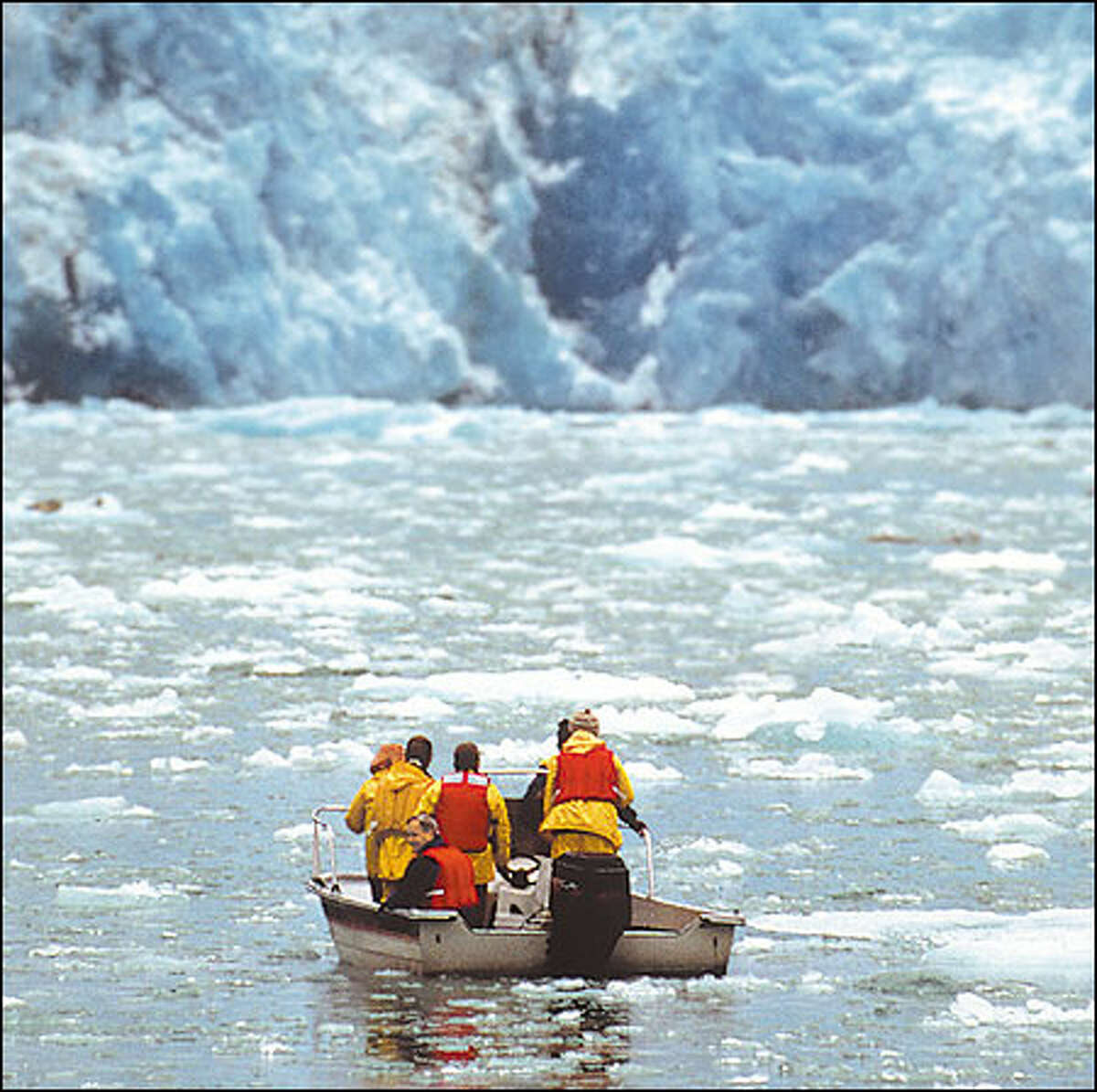A glacier wall towers over passengers from the Safari Quest as they explore the ice-choked Tracy Arm fjord. AMERICAN SAFARI CRUISES PHOTO