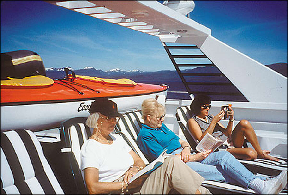 Relaxing and reading on the top deck of yach while under way in southeast Alaska. American Safari Cruises photo.
