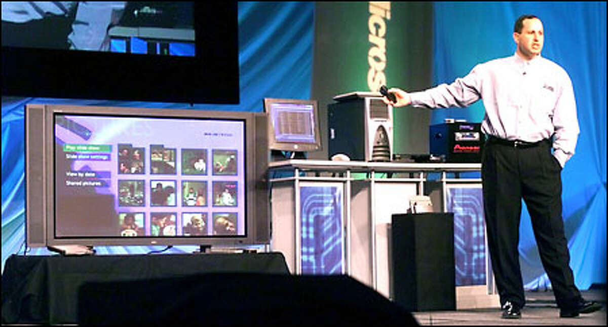 Steve Guggenheimer of Microsoft demonstrates the integration of wireless devices, PCs and home-entertainment centers during a conference in Seattle yesterday.
