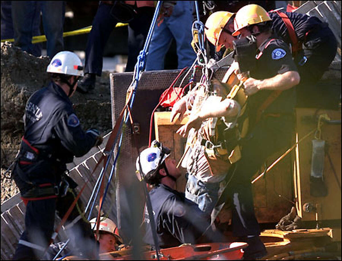 A construction worker is rescued after he was trapped for two hours yesterday in his track hoe when a bridge he was helping to demolish collapsed.