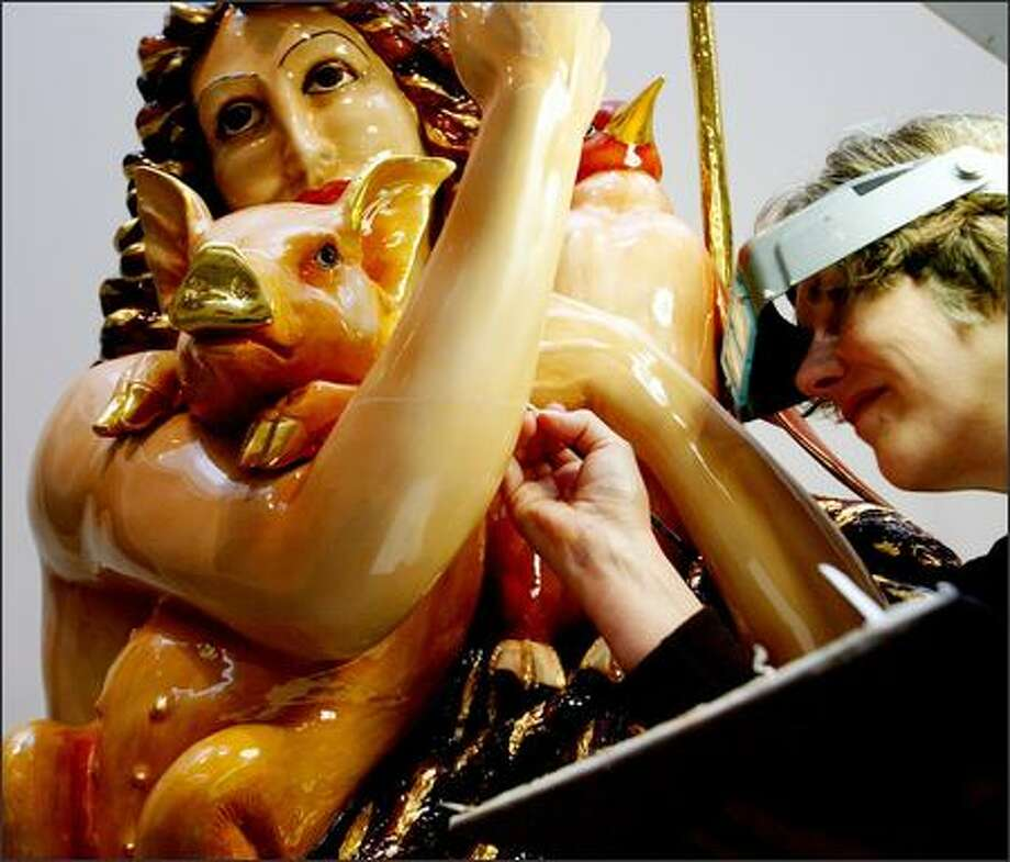 "Art conservationist Patricia Leavengood applies an epoxy with dry pigment to a crack in the arm of Jeff Koons' sculpture ""Saint John the Baptist"" during a restoration process after the statue was found damaged on arrival at Wright Exhibition Space in Seattle. Photo: Grant M. Haller, Seattle Post-Intelligencer / Seattle Post-Intelligencer"