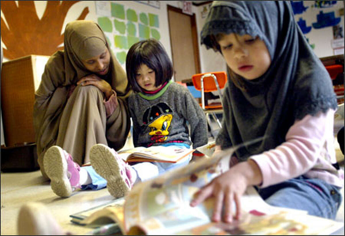 Teaching assistant Fadumo Muse looks at a book with Karen Vo, 5, while Lenorah Elmlinger, 4, examines a book on her own in the free day care program at White Center's Refugee and Immigrant Center yesterday.