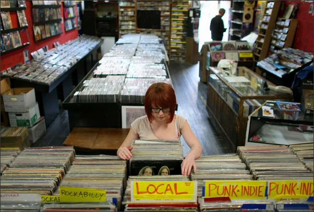 Brittany Wright sifts through the vast collection of records on Thursday at Bop Street Records in Ballard. Saturday is the first national Record Store Day.