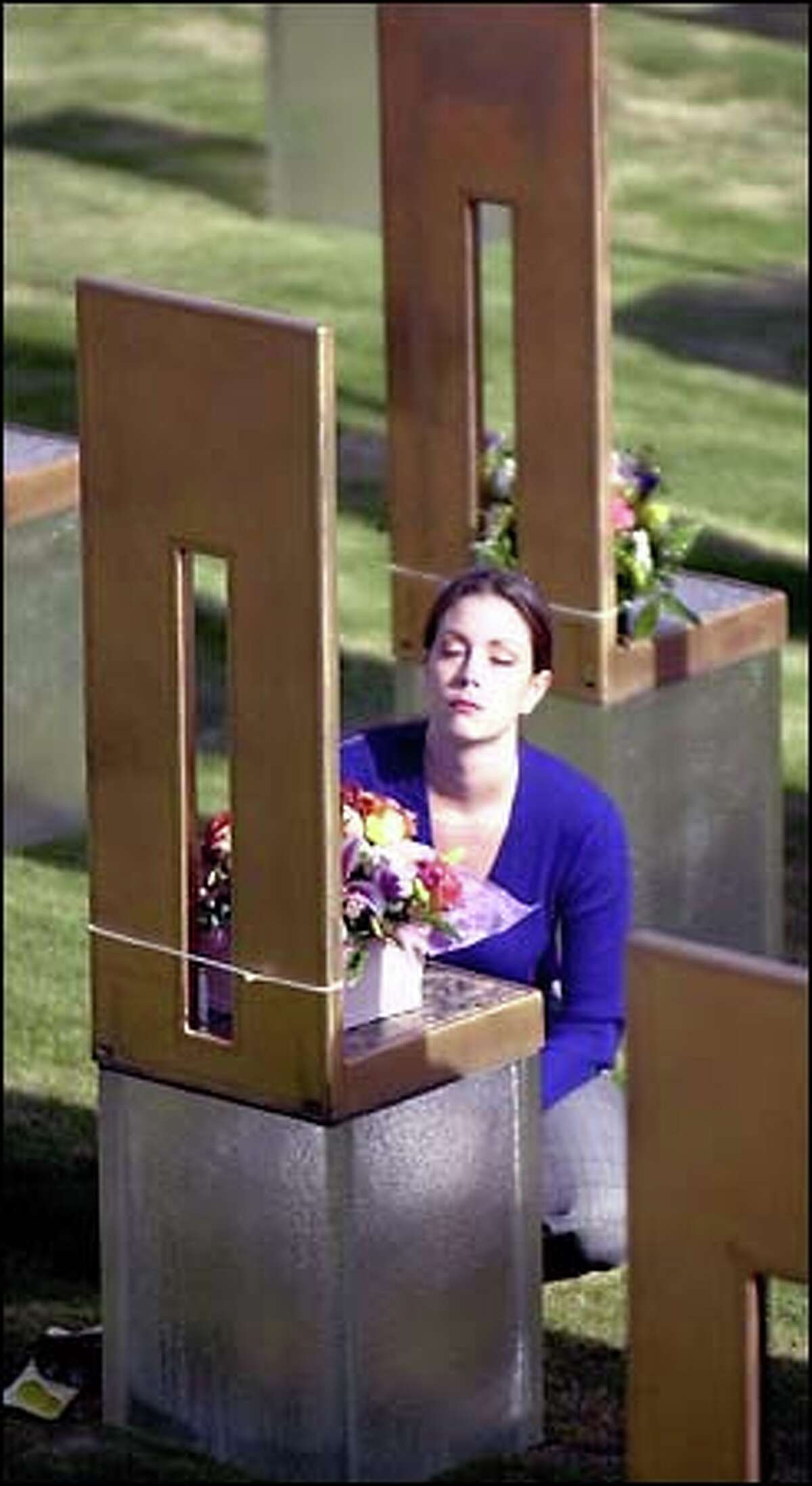 Jennifer Walker reflects as she kneels in front of the memorial chair for her father, who was killed in the Oklahoma City Federal Building bombing six years ago. Services to mark the anniversary of the bombing of the Alfred P. Murrah Federal Building were conducted at the Oklahoma City National Memorial site yesterday. Church bells chiming