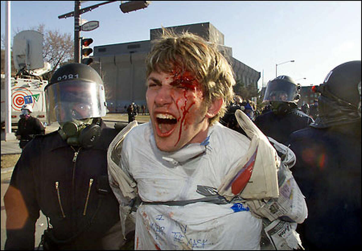 A bloodied protester is arrested by police after demonstrators and riot police clashed outside the grounds.