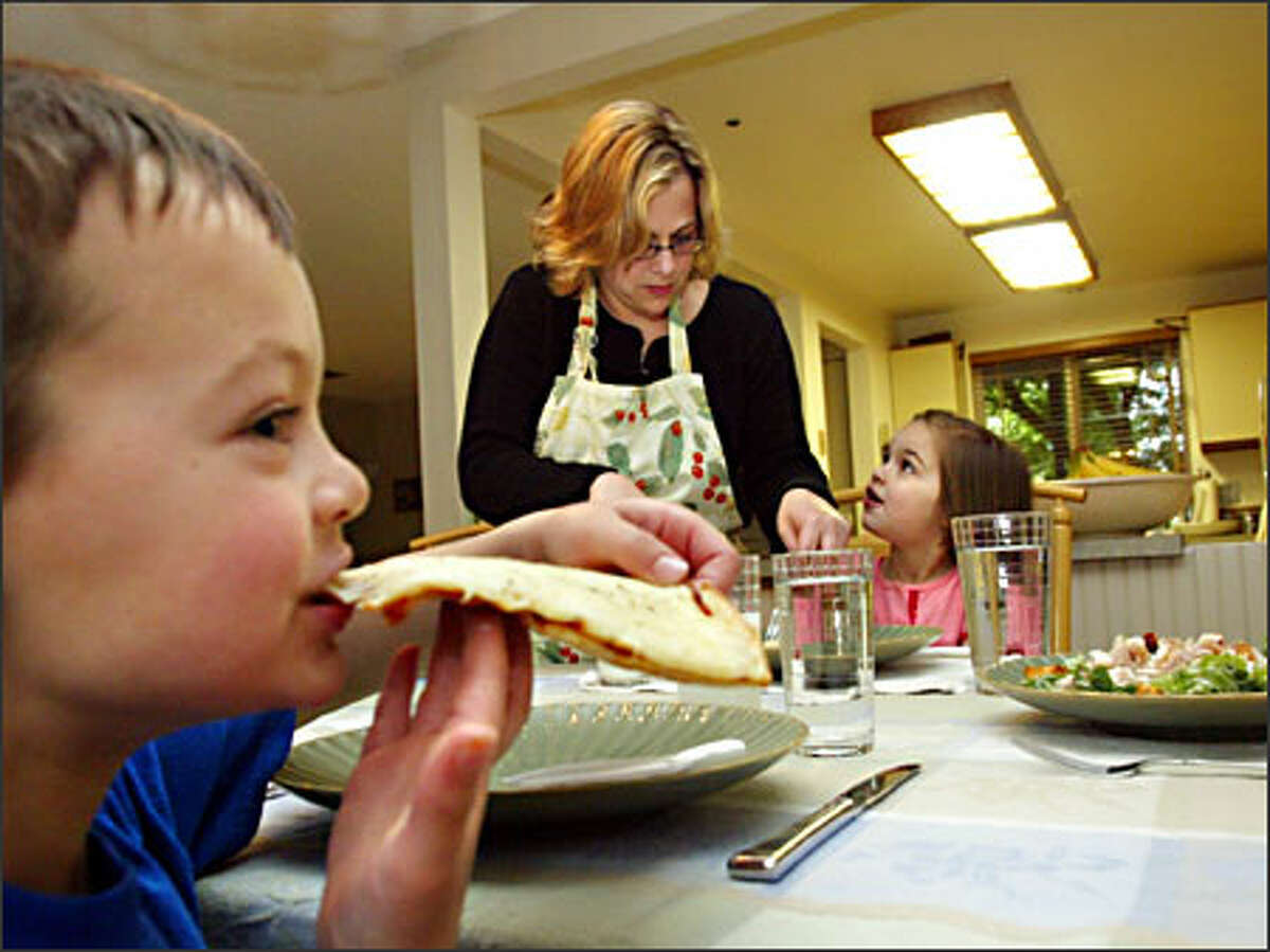 Jennifer Fisher of Bellevue serves homemade gluten-free pizza to her kids, Sam and Megan. Diagnosed with celiac disease, or gluten intolerance, Megan showed marked improvement days after going on a gluten-free diet.