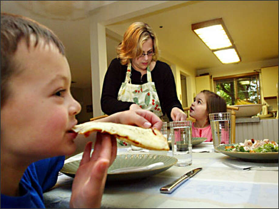Jennifer Fisher of Bellevue serves homemade gluten-free pizza to her kids, Sam and Megan. Diagnosed with celiac disease, or gluten intolerance, Megan showed marked improvement days after going on a gluten-free diet. Photo: Karen Ducey, Seattle Post-Intelligencer / Seattle Post-Intelligencer
