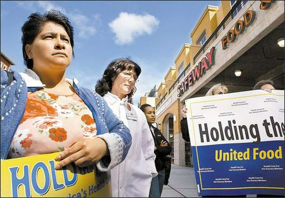 Rosemary Rosas, far left, and Mary Ann Schroeder rally outside the lower Queen Anne Safeway store yesterday. The workers are trying to preserve affordable health care benefits. Rosas, a checker, has worked for Safeway for a year and Schroeder has been a meat wrapper 10 years.