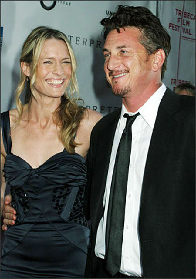 "Sean Penn, looking amazingly cheerful, and wife Robin Wright Penn arrive for the premiere of his new film, ""The Interpreter,"" Tuesday at the Tribeca Film Festival in New York. This 12-day festival is featuring more than 250 films. The event includes a Family Festival Street Fair that's expected to bring thousands to lower Manhattan. (TINA FINEBERG/AP) Photo: Associated Press / Associated Press"