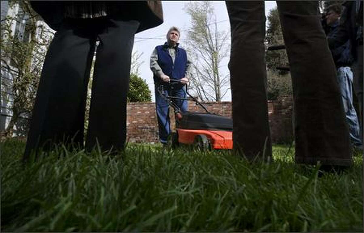 Mayor Greg Nickels shows off his electric lawn mower. Seattle residents who recycle their old gas mowers by May 15 will receive a $25 rebate coupon on a new push or electric mower.