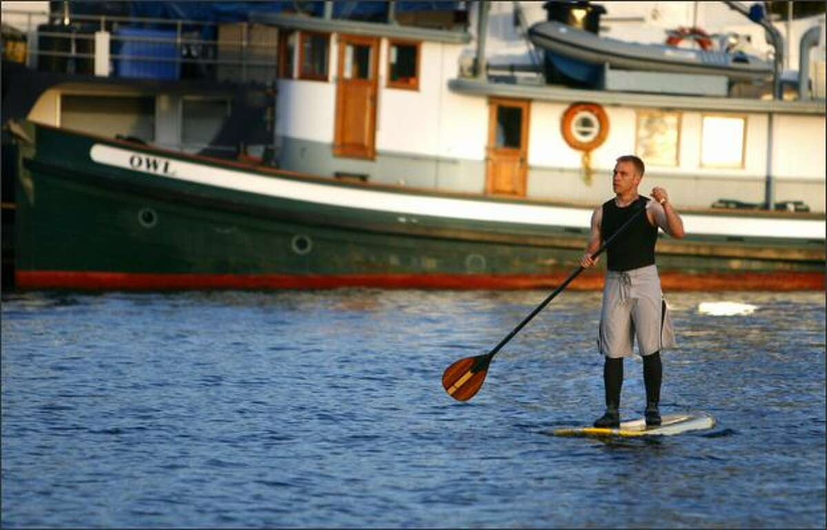 A paddle boarder takes advantage of the warm temperature and calm water to practice his sport on Lake Union in Seattle. The challenging sport combines balance and upper body strength.