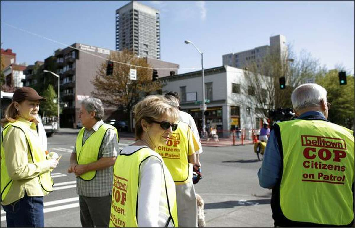 Greta Fagerland, center, looks around as members of Belltown Citizens on Patrol, or COP, march on Second Avenue on Tuesday in Belltown. Seattle police recently arrested more than 30 members of a Honduran drug gang in the neighborhood and residents are hoping to continue to clean up the area.