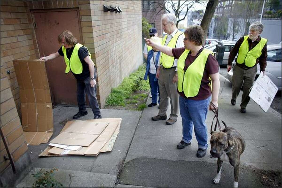 Members of Belltown COP, including Brett Paulson, left, and Janet Welt, with her dog Dolly, clean up cardboard left in a doorway during a community patrol on Second Avenue.