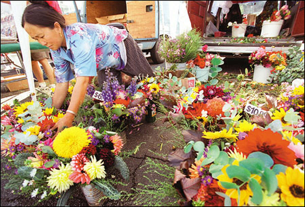 Mai Moua of Monroe adjusts some of the flowers she was selling last year at the Farmer's Market in Columbia City. The market, which is one of the success stories of the renaissance of the diverse Rainier Valley community, will reopen for the season next month.