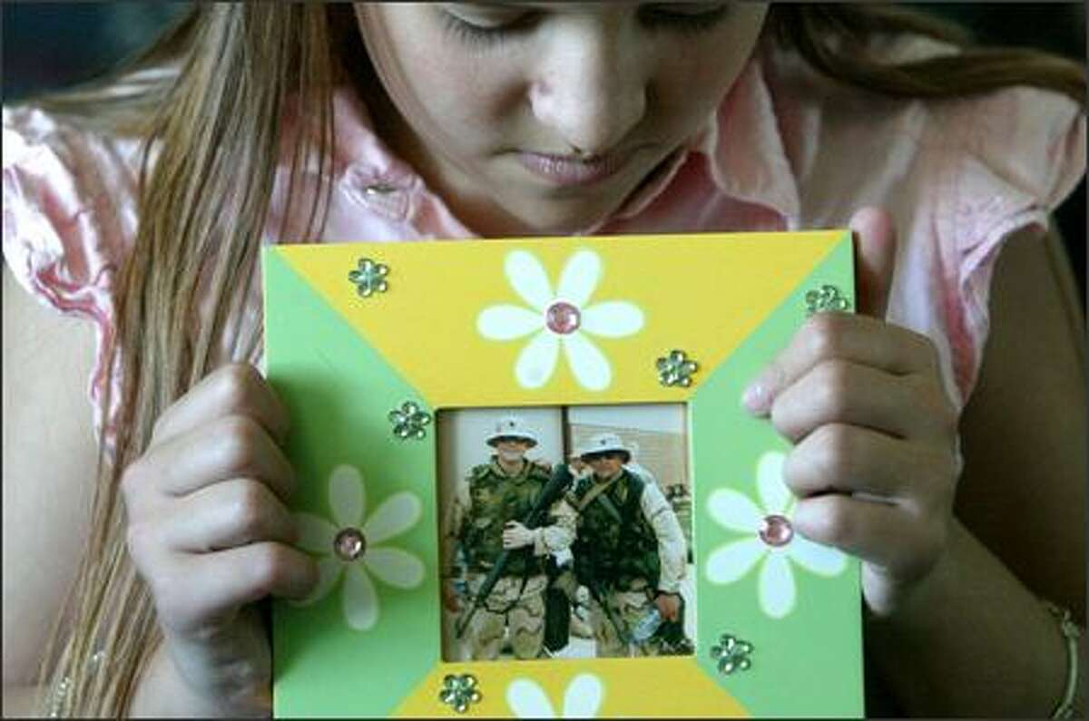 Sarah Kelly, 11, holds her favorite picture of her father, Spc. Wade Kelly, at right, of the 1161st Transportation Unit of the National Guard. The photo was taken while he was in Germany last year just before his unit left for Iraq. The other man in the photo is Wade Kelly's friend.