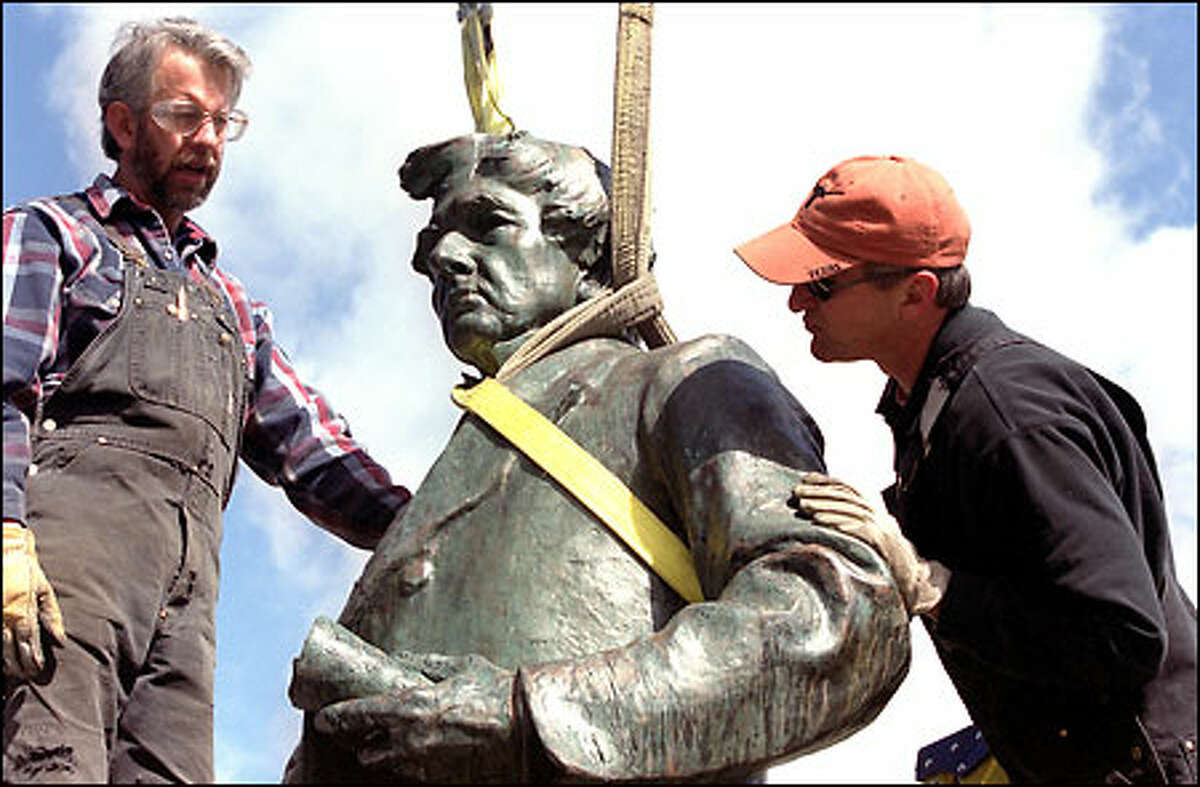 Jim Kristjanson, left, and Larry Tate of Fabrication Specialties Limited strap up the sculpture of William H. Seward before it is put back on its base in Volunteer Park. The sculpture was damaged during last year's earthquake.