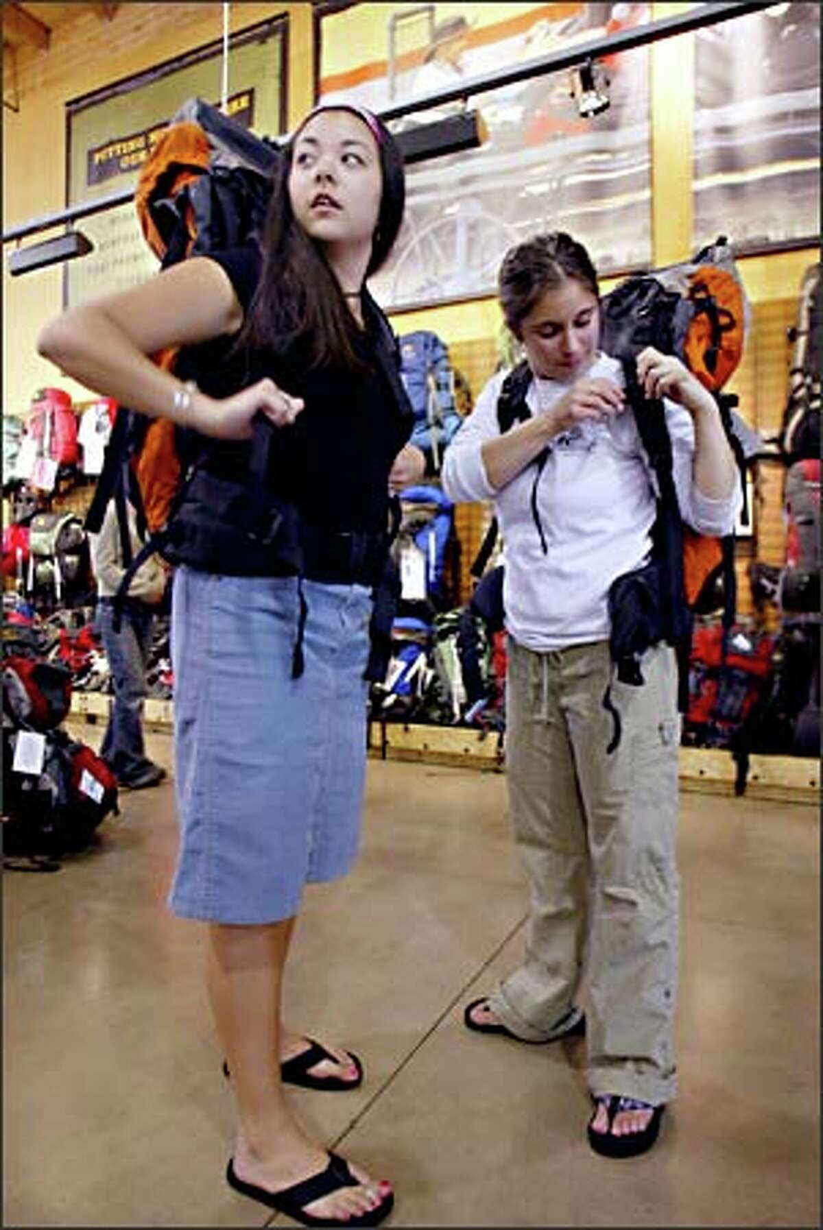 With her eyes on the store mirror, Shannon Hannon fits herself with a Lowe Alpine Sirocco 1 women's backpack as friend Jamie Higbee adjusts a strap on another pack at the Seattle REI store Thursday. The women are headed to Alaska to be camp counselors in June.