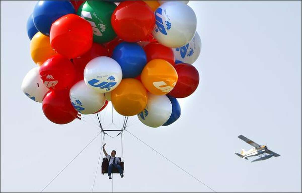 Seattle radio personality Don O'Neill of KIRO's Ron and Don Show goes airborne in a chair tied to more than 60 helium-filled balloons on Friday during a publicity event for a new Disney movie at Gasworks Park. Disney-Pixar's new film, UP, is about the adventures of a balloon salesman who ties balloons to his house.