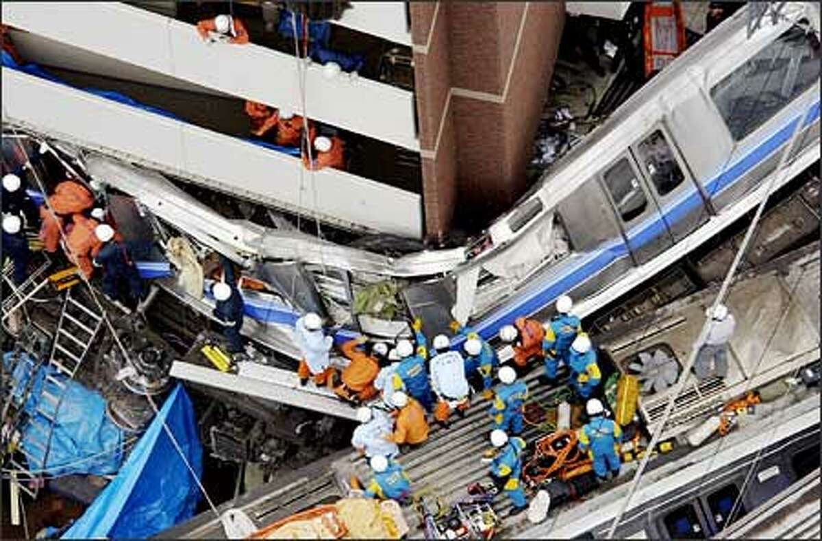 Rescuers try to rescue people trapped in the derailed train car after a derailment at Amagasaki, near Osaka, western Japan. A packed commuter train jumped the tracks in western Japan on Monday and hurtled into an apartment complex, killing at least 50 people and injuring more than 340 others in the deadliest rail accident here in four decades. (AP Photo/Kyodo News)