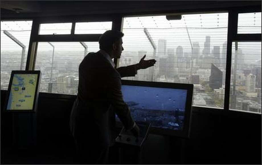 Eric Perret, SkyQ project manager, demonstrates some of the new technology geared toward tourists visiting the Space Needle at a prelaunch briefing Tuesday. SkyQ, a $2 million project that includes five interactive kiosks giving visitors atop the Space Needle the opportunity to view Seattle in unique ways, will open to the public today. Photo: Andy Rogers, Seattle Post-Intelligencer / Seattle Post-Intelligencer