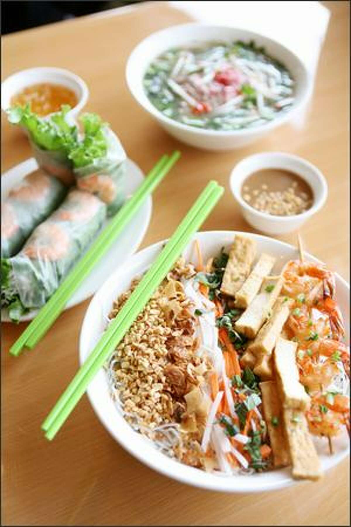 The menu at Time 4 Pho in Magnolia includes, clockwise from lower right: bun (noodle salad) with tofu and shrimp skewer, spring rolls and pho with steak.
