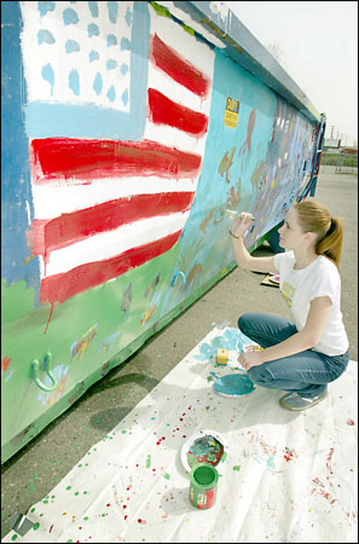 """Vanessa Martin, 15, paints a recycling box during a """"Take Your Daughters to Work Day"""" beautification project at the South Seattle solid-waste transfer facility. Vanessa's father, Alejandro, works at the transfer station."""