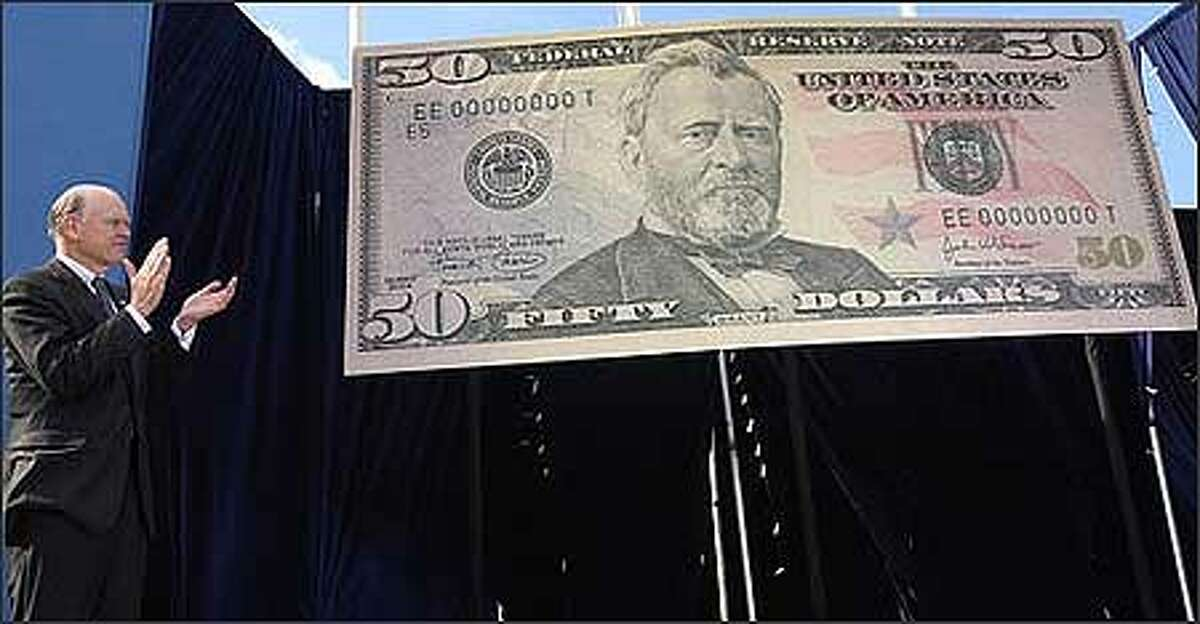 Treasury Secretary John W. Snow applauds the unveiling of the new $50 bill in Forth Worth, Texas, Monday. The redesigned $50 is the same size and still features Ulysses S. Grant on the front and the U.S. Capitol on the back. But the borders around both Grant and the Capitol have been removed and the bill now has colors. (AP Photo/LM Otero)