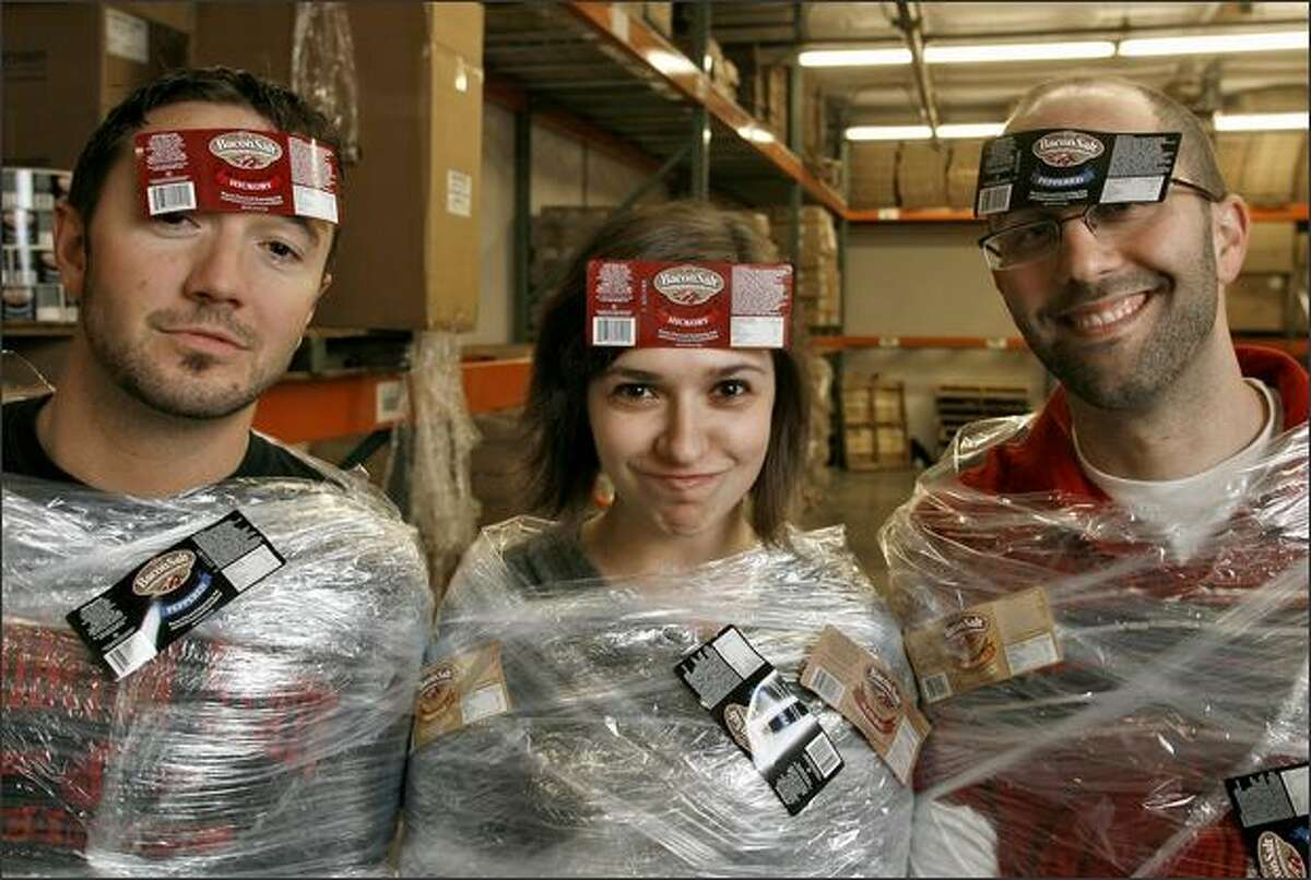Baconslinger Reilly Devine, left, Operbacons Manager Sarah Wayne and bacontrepreneur Dave Lefkow are ready for shipping at their Seattle headquarters.