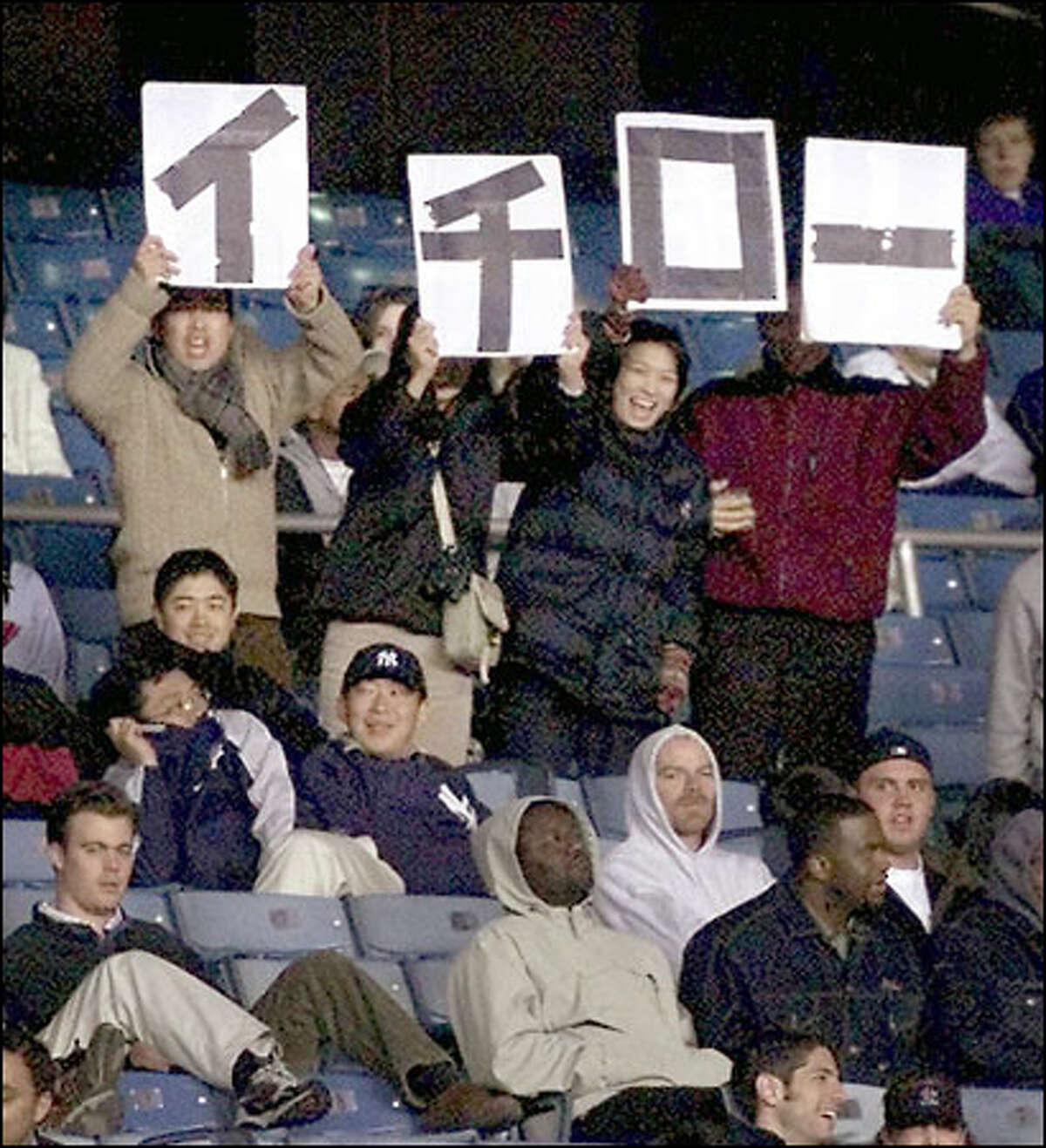 Fans of Mariners right fielder Ichiro Suzuki wave signs that spell Ichiro in the eighth inning of last night's game against the Yankees.