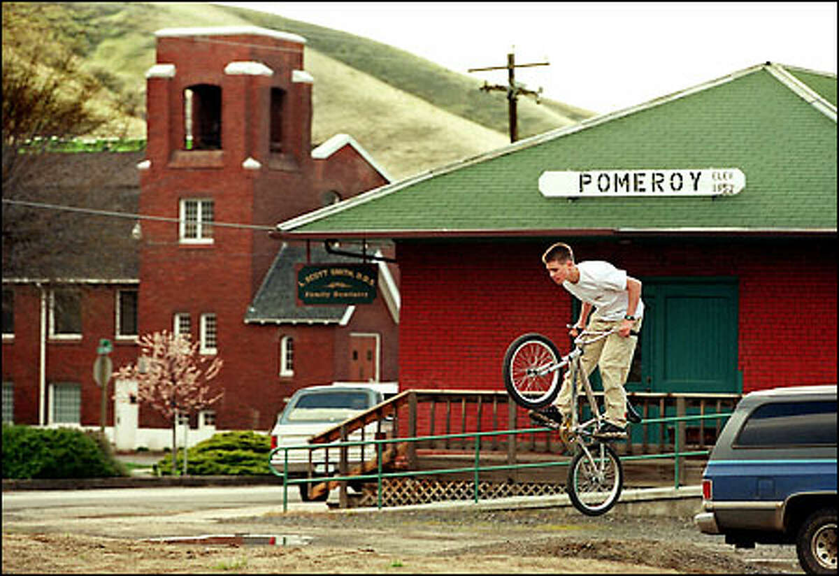 Brandon Baker, 14, does a jump on his bike outside the former Pomeroy train station, now occupied by a dentistry practice. The United Methodist Church is in the background.