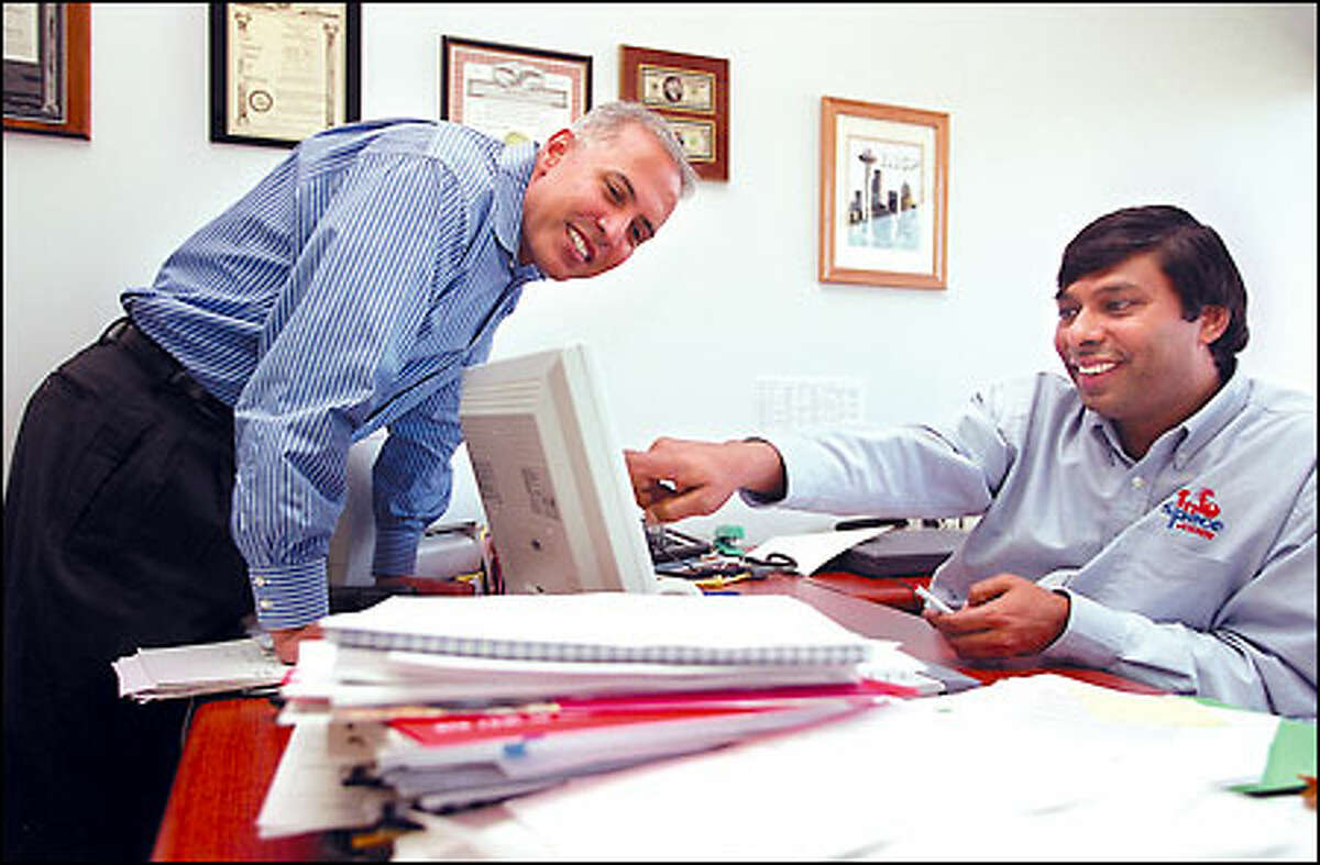 In happier times, then-newly named InfoSpace CEO Arun Sarin, left, and Naveen Jain.